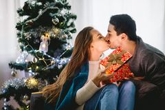Young sexy couple kissing in front of Christmas tree, woman unpacking present. Young sexy couple kissing in front of Christmas tree, women unpacking present Royalty Free Stock Photo