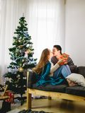 Young sexy couple kissing in front of Christmas tree, woman unpacking present. Young sexy couple kissing in front of Christmas tree, women unpacking present Stock Photos