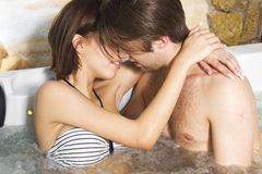 Young sexy couple kissing in the jacuzzi Stock Image