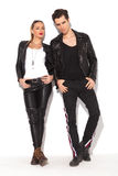 Young sexy couple in leather jackets posing. Standing against white wall Stock Photo