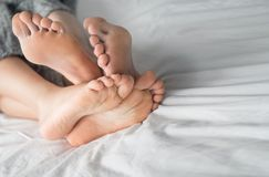 Young couple in love lying in bed in hotel, embracing on white sheets, close up legs, romantic mood. stock photos