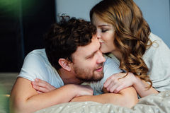 Young sexy couple in love lying in bed in hotel, embracing on white sheets, close up Royalty Free Stock Photography