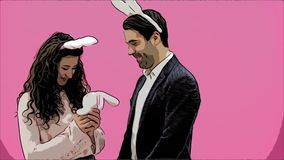 Young sexy couple on pink background. With bunny ears on the head. During this man gives a soft toy with a hare to his. Wife. Having kissed, looking at the stock footage