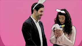 Young sexy couple on pink background. With hackneyed ears on the head. During this man gives a soft toy hare and colored. Decorative eggs to his wife. Having stock video footage