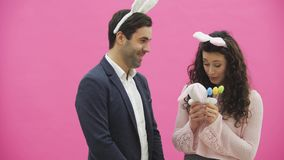 Young sexy couple on pink background. With hackneyed ears on the head. During this man gives a soft toy hare and colored. Decorative eggs to his wife. Having stock footage