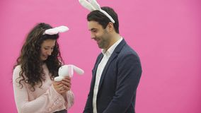 Young sexy couple on pink background. With hackneyed ears on the head. During this man gives a soft toy with a hare to. His wife. Having kissed looking at the stock footage