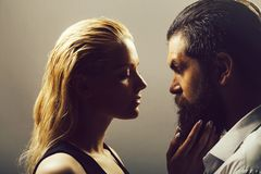 Young sexy couple. Of pretty women with blonde hair and handsome bearded men with long beard embracing on grey background royalty free stock images