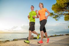 Running. Young couple is running along the promenade. they are doing their sport workout in the beautiful sundown along the beach. colorful dress, trees, water stock image