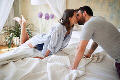 Young sexy couple in underwear having a kiss in bed in the morinig on valentines day. Intimacy, passion, erotic concept