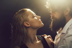 Young couple with wet hair. Young couple of pretty women with blonde wet hair and handsome bearded men with long beard embracing on dark studio background stock images