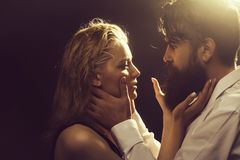 Young couple with wet hair. Young couple of pretty women with blonde wet hair and handsome bearded men with long beard embracing on dark studio background royalty free stock photo