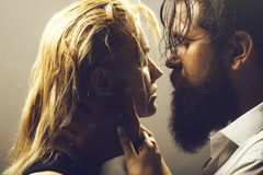 Young couple with wet hair. Young couple of pretty women with blonde wet hair and handsome bearded men with long beard embracing on grey studio background royalty free stock photography