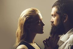 Young couple. Of pretty women with blonde hair and handsome bearded men with long beard embracing on grey background royalty free stock photography