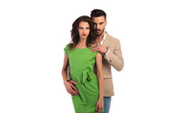Young cuple looking at the camera. Men behind women wit hand on her shoulder, on white background stock photo