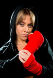 Young sexy  dangerous boxing girl wrapping hands and wrists female combat boxer. Young sexy angry and dangerous looking boxing girl wrapping hands and wrists Stock Photo
