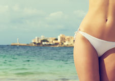 Young sexy female body on sea background. Royalty Free Stock Image