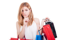 Young female show you to keep silence. Young shopping female show you to keep silence while buying expensive gifts isolated on white background stock photos