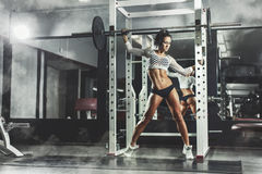 Young sexy fitness brunette girl in the gym posing and relaxing. Young sexy fitness brunette girl in the gym posing and holding the barbell and relaxing on smoke Royalty Free Stock Images