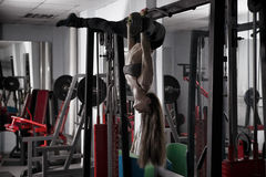 Young fitness girl pulls up in the gym and performing exercises on the horizontal bar Stock Photos