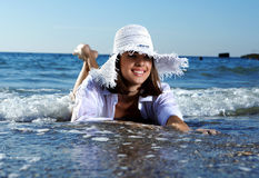 Young girl on the beach. Young girl with a smile on the beach lying in the water stock image