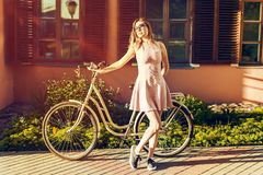 Young girl on a bicycle in full length posing portrait in pink dress. she is satisfied with the sun royalty free stock image