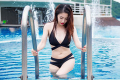 Young sexy girl in bikini going out of swimming pool. Stock Images