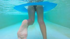 Young Sexy Girl in Bikini Swimsuit Swimming in Pool on Rubber Ring. Underwater Slowmotion Footage. Thailand. Young Sexy Girl in Bikini Swimsuit Swimming in Pool stock footage