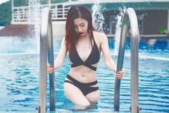 Young girl in black bikini going out of swimming pool. stock image