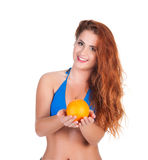 Young sexy girl in blue bikini and shawl holding orange Stock Image