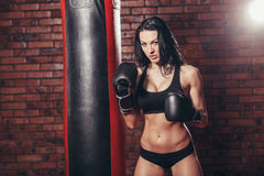 Young sexy girl with boxing gloves, punching bag Stock Photo
