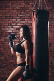 Young sexy girl with boxing gloves, punching bag Royalty Free Stock Photography