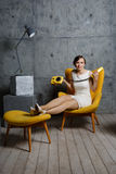 Young sexy girl in a chair with phone Royalty Free Stock Image