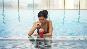 Young sexy girl drinking cocktail in pool stock footage