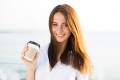 Young girl drinking coffee on seaside stock photography