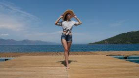 Young sexy girl in a hat and shorts walking on the pier. In Turkey stock video