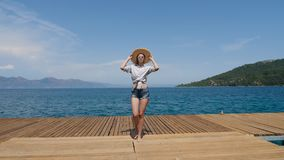 Young sexy girl in a hat and shorts walking on the pier. In Turkey stock video footage