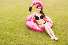 Young and sexy girl having fun and laughing and having fun on the grass near the pool on an inflatable pink flamingo in a bathing. Suit and sunglasses in summer Stock Images