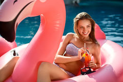 Young and girl having fun and laughing on an inflatable giant pink flamingo pool float mattress with a cocktail Royalty Free Stock Image