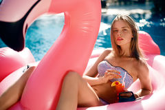 Young and sexy girl having lies in the sun an inflatable giant pink flamingo pool float mattress with a cocktail glass Royalty Free Stock Photos