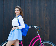 Young girl with long hair with blue backpack standing near vintage pink bicycle, have fun and good mood looking in camera and stock photos