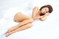 Young sexy girl lying on white bed Royalty Free Stock Image