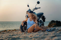 Young sexy girl with motorcycle. Young sexy girl on the beach with the motorbike Stock Image