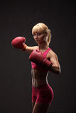 Young sexy girl over black background with boxing gloves Royalty Free Stock Image