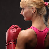 Young sexy girl over black background with boxing gloves Royalty Free Stock Images