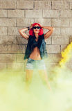 Young sexy girl in red wig and black jacket having fun in yellow smoke Royalty Free Stock Images
