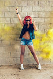 Young sexy girl in red wig and black jacket having fun in yellow smoke Stock Image