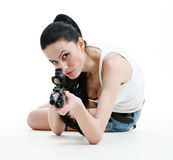 Young sexy girl shoots with a sniper rifle. Young sexy girl shoots with a sniper rifle, isolated with white background Royalty Free Stock Images