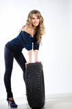 Young sexy girl sitting on the car wheel Royalty Free Stock Photography