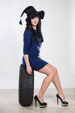 Young sexy girl sitting on the car wheel Stock Photos