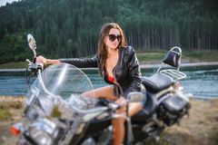 Young sexy girl sitting on custom made cruiser motorcycle. Portrait of young sexy lady with long hair wearing leather jacket and short shorts sitting on custom Royalty Free Stock Photos